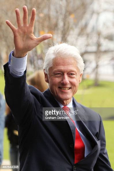 Former US President Bill Clinton waves as he leaves the 20th International AIDS Conference at The Melbourne Convention and Exhibition Centre on July...