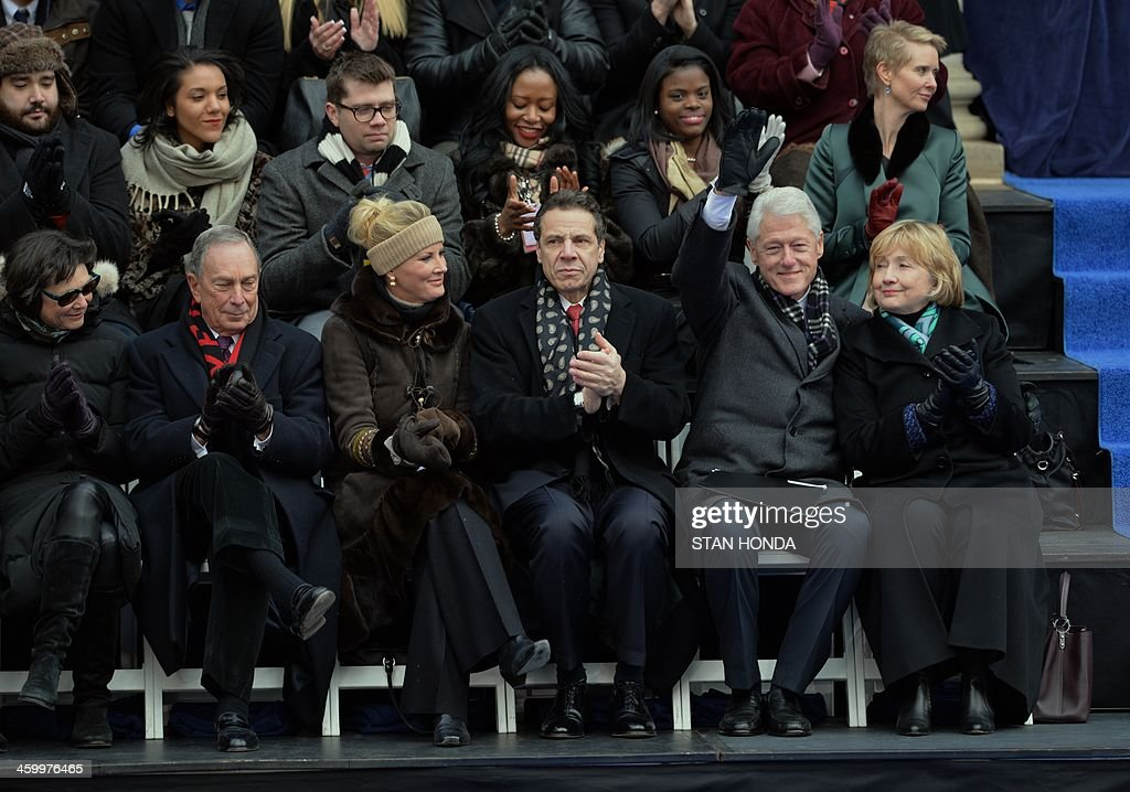 Former US President Bill Clinton (2nd R) waves with his wife Hillary Clinton at the inauguration of New York City Mayor Bill de Blasio on the steps of City Hall in Lower Manhattan January 1, 2014 in New York. Seated are New York State Governor Andrew Cuomo (C), his girlfriend cooking show host Sandra Lee, outgoing New York City Mayor Michael Bloomberg (2nd L) and his girlfriend Diana Taylor (L). AFP PHOTO/Stan HONDA