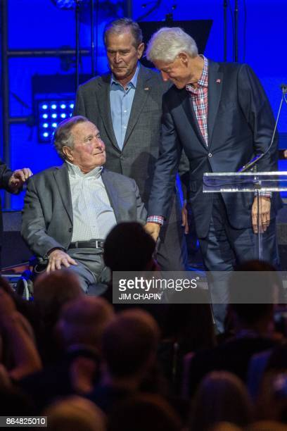 Former US President Bill Clinton with President George W Bush greets President George H W Bush during the Hurricane Relief concert in College Station...