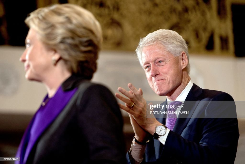TOPSHOT - Former US President Clinton listens while his wife, former Democratic US Presidential candidate Hillary Clinton speaks to staff and supporters at the New Yorker hotel after her defeat in the presidential election November 9, 2016 in New York. / AFP / Brendan Smialowski