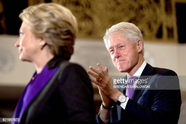 TOPSHOT Former US President Clinton listens while his wife former Democratic US Presidential candidate Hillary Clinton speaks to staff and supporters...