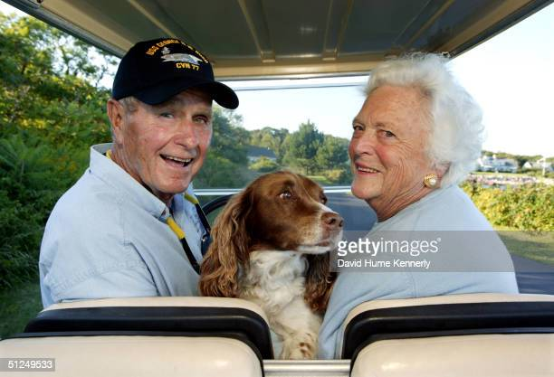 Former US president George H W Bush and wife Barbara Bush cruise in the back of a golf cart with their dog Millie at their home at Walker's Point...