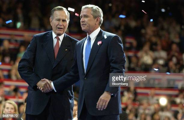 Former US President George Herbert Walker Bush left congratulates his son current US President George W Bush during the final session of the...