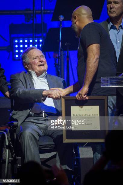 Former US President George HW Bush congratulates Daily Point of Light Award recipient Derek Auguste during the Hurricane Relief concert in College...