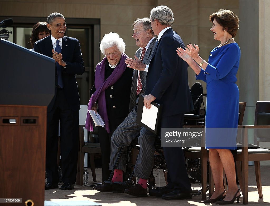Former US President George HW Bush is helped to stand up to acknowledge the crowd by his wife former first lady Barbara Bush and his son former...