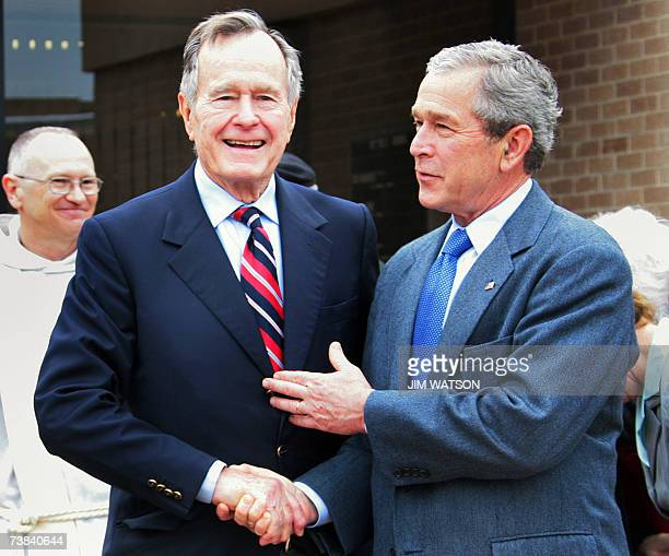 Former US president George HW Bush shakes hands with his son US President George W Bush as they depart the military chapel following Easter Services...