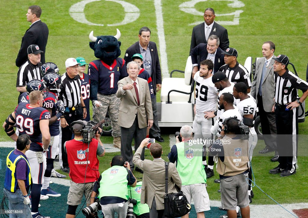 Former U.S. President George H.W. Bush (back, right) watches as former President <a gi-track='captionPersonalityLinkClicked' href=/galleries/search?phrase=George+W.+Bush&family=editorial&specificpeople=122011 ng-click='$event.stopPropagation()'>George W. Bush</a> flips the coin for the Houston Texans game against the Oakland Raiders on November 17, 2013 at Reliant Stadium in Houston, Texas.