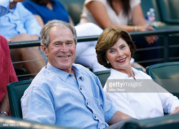 Former US president George W Bush and former First Lady Laura Busy wait for the start of the game between the Seattle Mariners and the Texas Rangers...