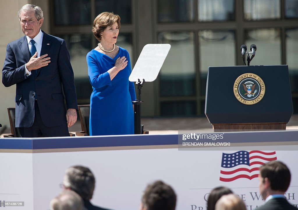Former US President George W. Bush and Laura Bush listen to the National Anthem during a dedication ceremony at the George W. Bush Library and Museum on the grounds of Southern Methodist University April 25, 2013 in Dallas, Texas. The Bush library is dedicated to chronicling the presidency of the United State's 43rd President, George W. Bush. AFP PHOTO/Brendan SMIALOWSKI
