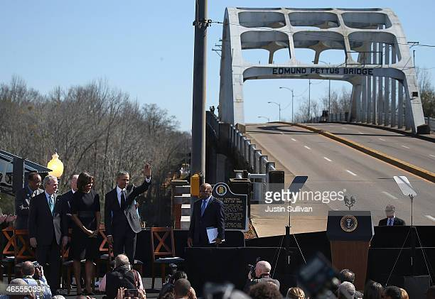 Former US president George W Bush first lady Michelle Obama US president Barack Obama and US Rep John Lewis greet the crowd during a commemoration of...