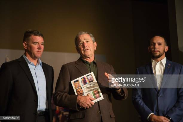 Former US President George W Bush holds up a print copy of his 'Portraits of Courage' exhibit as he stands with several of the veterans he painted at...