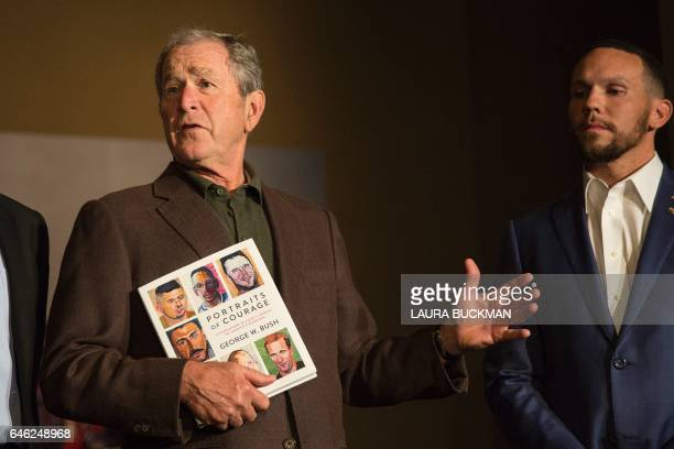 Former US President George W Bush holds up a print copy of his 'Portraits of Courage' painting exhibit as he stands next to one of the veterans...