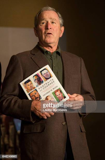 Former US President George W Bush holds up a print copy of his 'Portraits of Courage' painting exhibit at a press preview at the George W Bush...