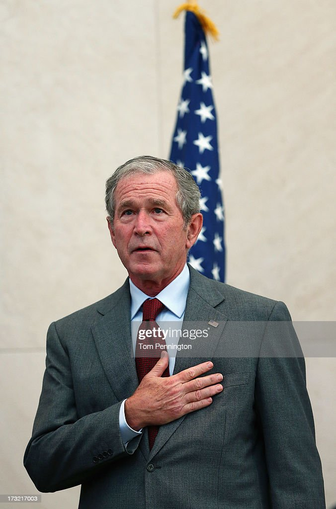 Former U.S. President <a gi-track='captionPersonalityLinkClicked' href=/galleries/search?phrase=George+W.+Bush&family=editorial&specificpeople=122011 ng-click='$event.stopPropagation()'>George W. Bush</a> puts his hand over his heart during the National Anthm at a immigration naturalization ceremony held at the <a gi-track='captionPersonalityLinkClicked' href=/galleries/search?phrase=George+W.+Bush&family=editorial&specificpeople=122011 ng-click='$event.stopPropagation()'>George W. Bush</a> Presidential Center on July 10, 2013 in Dallas, Texas. Bush delivered keynote remarks during the naturalization ceremony, where 20 candidates took the oath of allegiance and became American citizens.