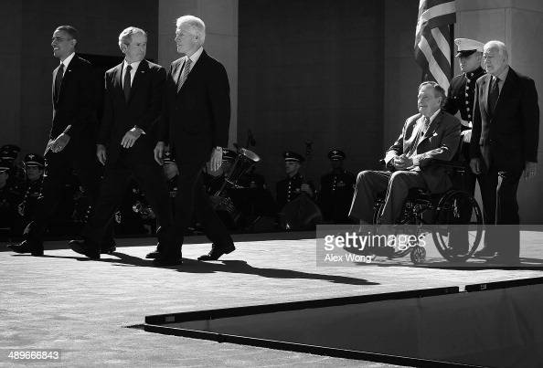 Former US President George W Bush turns around and checks on his father and former President George HW Bush as all five living presidents including...
