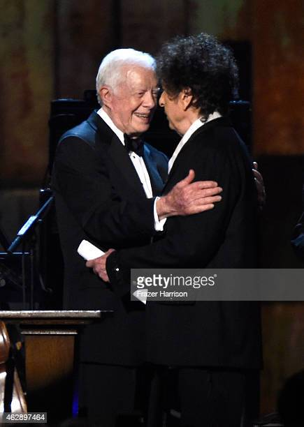 Former US President Jimmy Carter and honoree Bob Dylan appear onstage at the 25th anniversary MusiCares 2015 Person Of The Year Gala honoring Bob...