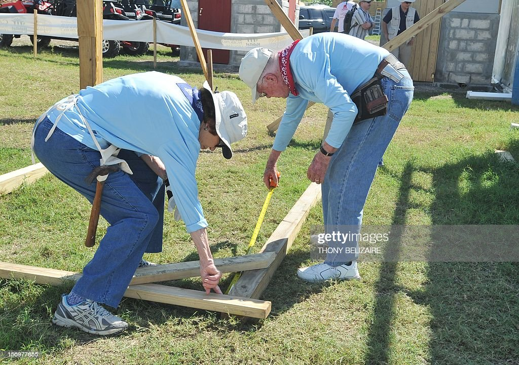 Former US president Jimmy Carter and wife Rosalynn Carter help build a house as they visit the construction site of houses being built by Carter's Habitat for Humanity foundation for victims of the January 2010 earthquake in Leogane, 33km south of Port-au-Prince, on November 26, 2012. AFP PHOTO Thony BELIZAIRE