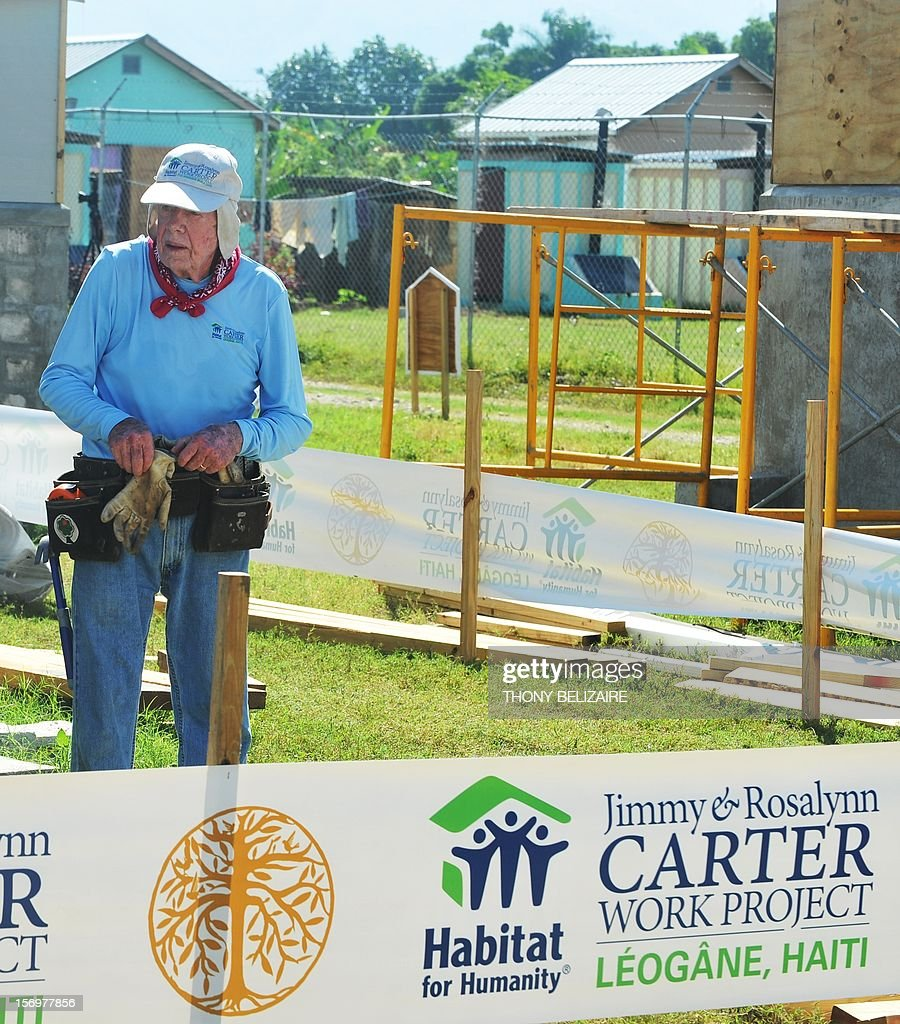 Former US president Jimmy Carter helps build a house as he and his wife Rosalynn visit the construction site of houses being built by Carter's Habitat for Humanity foundation for victims of the January 2010 earthquake in Leogane, 33km south of Port-au-Prince, on November 26, 2012. AFP PHOTO Thony BELIZAIRE