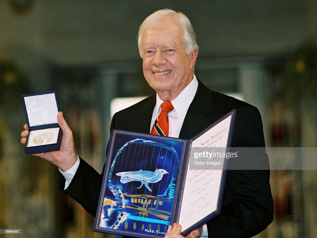 Former US President Jimmy Carter holds up his Nobel Peace Prize December 10 2002 in Oslo Norway Carter was recognized for many years of public...