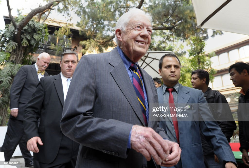 Former US President Jimmy Carter (C) leaves after a press conference in Kathmandu on April 1, 2013. Carter is in Kathmandu on a four-day visit. AFP PHOTO/Prakash MATHEMA