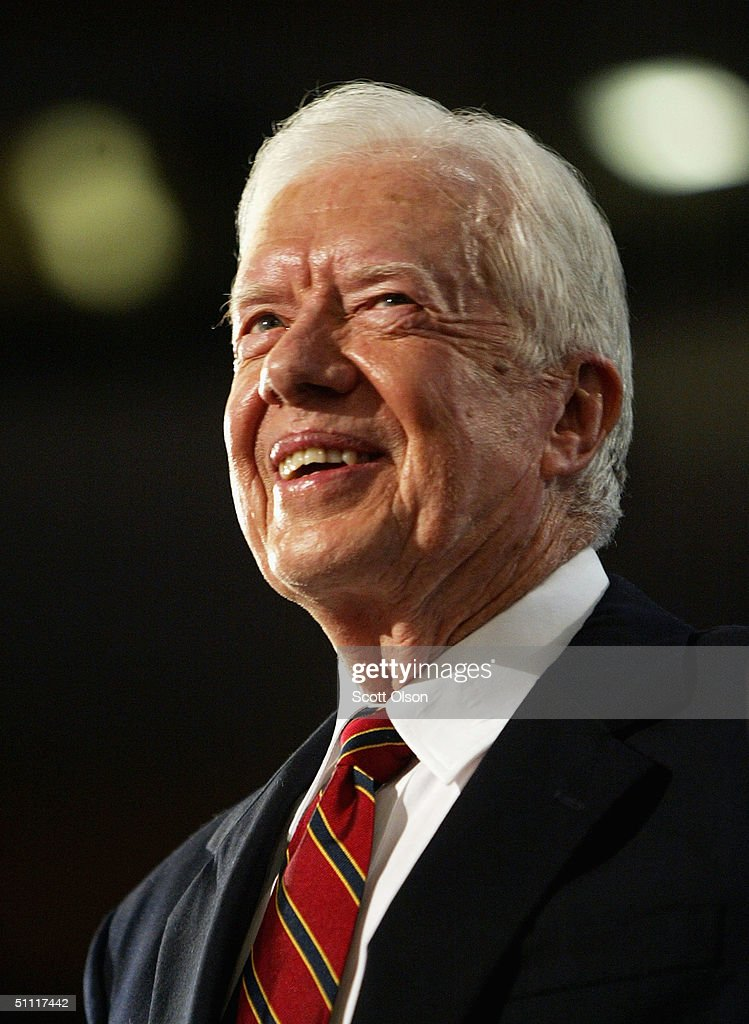 Former US President Jimmy Carter reacts onstage on opening night at the Democratic National Convention July 26 2004 at the FleetCenter in Boston...