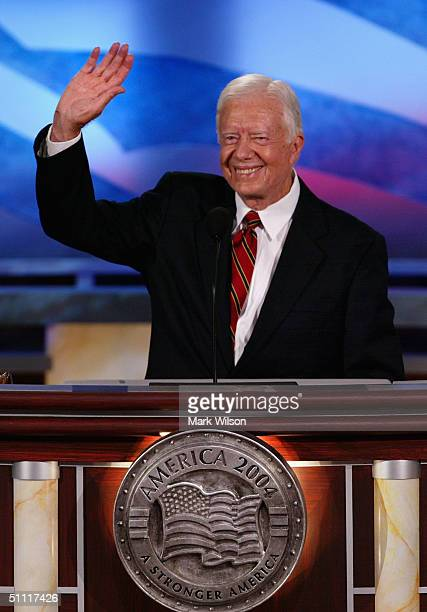 Former US President Jimmy Carter waves to the audience after speaking on opening night of the Democratic National Convention July 26 2004 at the...