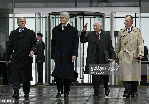 Former US presidents Bill Clinton George HW Bush and Jimmy Carter and current President George W Bush arrive for the dedication and opening of the...