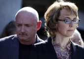 Former US Rep Gabby Giffords and her husband Mark Kelly attend a news conference outside Safeway grocery store where they asked Congress to provide...