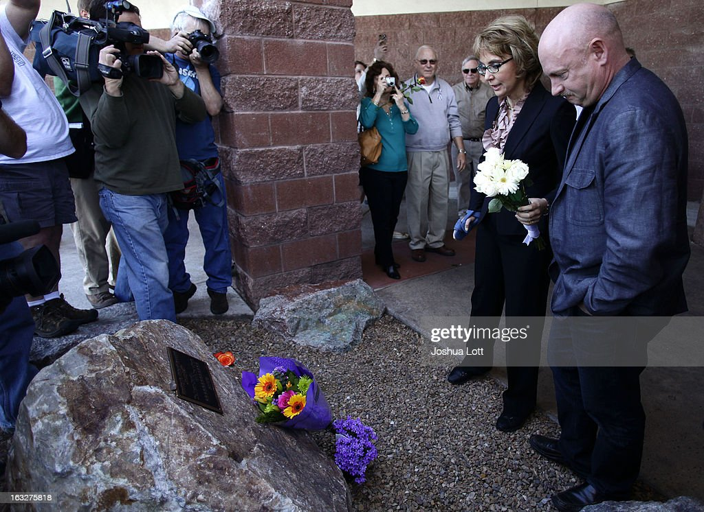 Former U.S. Rep. Gabby Giffords prepares to place flowers at a memorial with her husband <a gi-track='captionPersonalityLinkClicked' href=/galleries/search?phrase=Mark+Kelly+-+Astronaut+and+Gun+Control+Advocate&family=editorial&specificpeople=566699 ng-click='$event.stopPropagation()'>Mark Kelly</a> before attending a news conference outside Safeway grocery store where they asked Congress to provide stricter gun control in the United States on March 6, 2013 in Tucson, Arizona. Giffords and Kelly were joined by survivors of the Tucson shooting that took place there two years ago when six people were killed and Giffords herself was shot in the head.