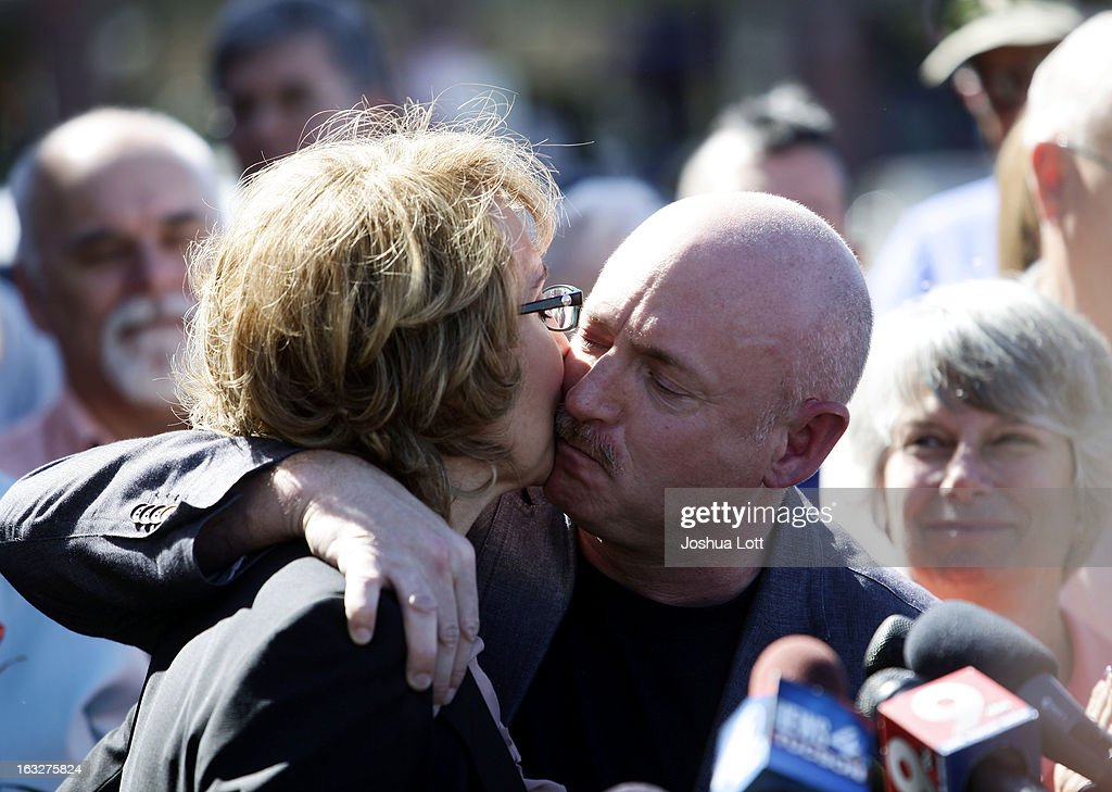 Former U.S. Rep. Gabby Giffords receives a kiss from her husband <a gi-track='captionPersonalityLinkClicked' href=/galleries/search?phrase=Mark+Kelly+-+Astronaut+and+Gun+Control+Advocate&family=editorial&specificpeople=566699 ng-click='$event.stopPropagation()'>Mark Kelly</a> during a news conference outside Safeway grocery store where they asked Congress to provide stricter gun control in the United States on March 6, 2013 in Tucson, Arizona. Giffords and Kelly were joined by survivors of the Tucson shooting that took place there two years ago when six people were killed and Giffords herself was shot in the head.