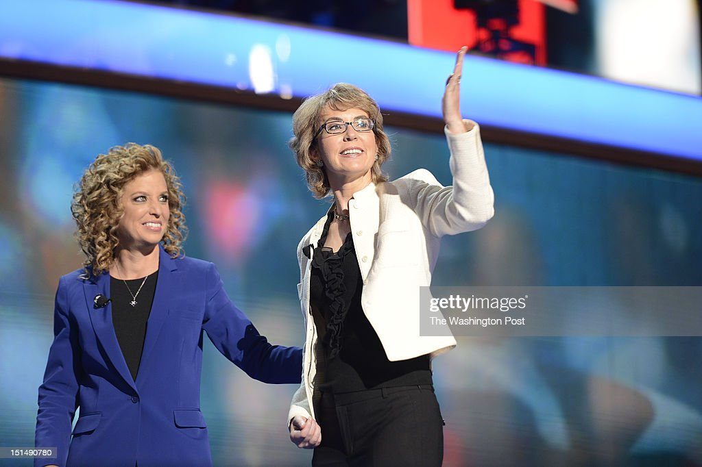 Former U.S. Rep. Gabrielle Giffords (D-AZ) (right) blows kisses to the crowd at the 2012 Democratic National Convention at the Time Warner Center on September 6, 2012 in Charlotte, North Carolina. Giffords led the pledge of allegiance. She is escorted by U.S. Rep. Debbie Wasserman Schultz.