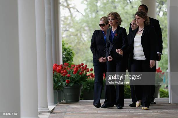Former US Rep Gabrielle Giffords escorts family members of Newtown CT shooting victims before US President Barack Obama makes a statement on gun...