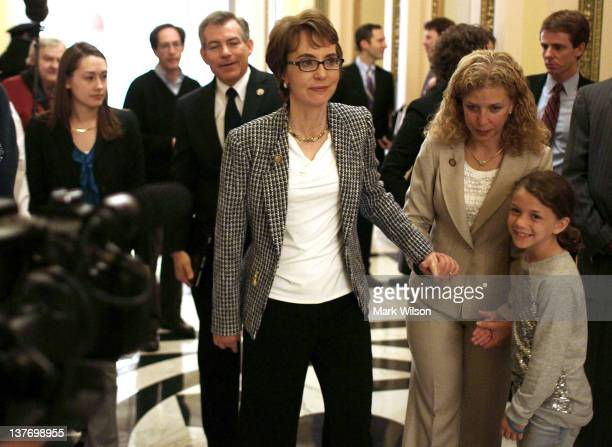 Former US Rep Gabrielle Giffords is excorted down the hall by Rep Debbie Wasserman Schultz after she resigned from the House of Representatives on...