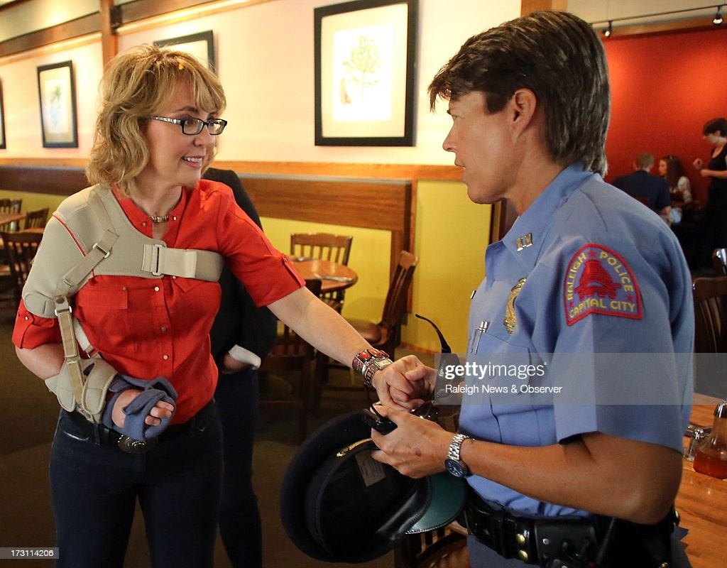 Former U.S. Rep. Gabrielle Giffords speaks Raleigh Police Department Captain Paula O'Neal after a roundtable at The Pit Authentic Barbecue in Raleigh, North Carolina, Sunday, July 7, 2013.