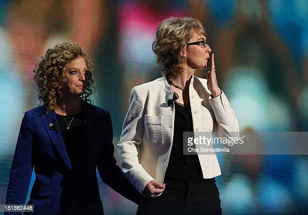 Former US Rep Gabrielle Giffords walks on stage with Democratic National Committee Chair US Rep Debbie Wasserman Schultz during the final day of the...