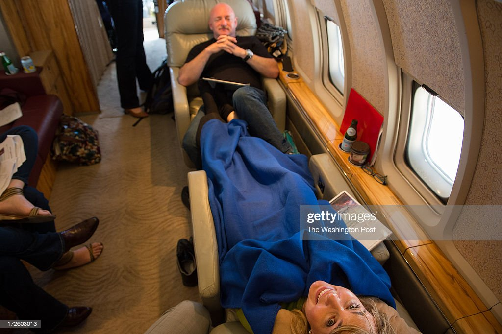 Former U.S. Representative Gabrielle Giffords and her husband Mark Kelly share a laugh with her nurse, not shown, flying between Las Vegas to Anchorage during their Americans for Responsible Solutions tour in Las Vegas, Nevada, on Monday, July 1, 2013.