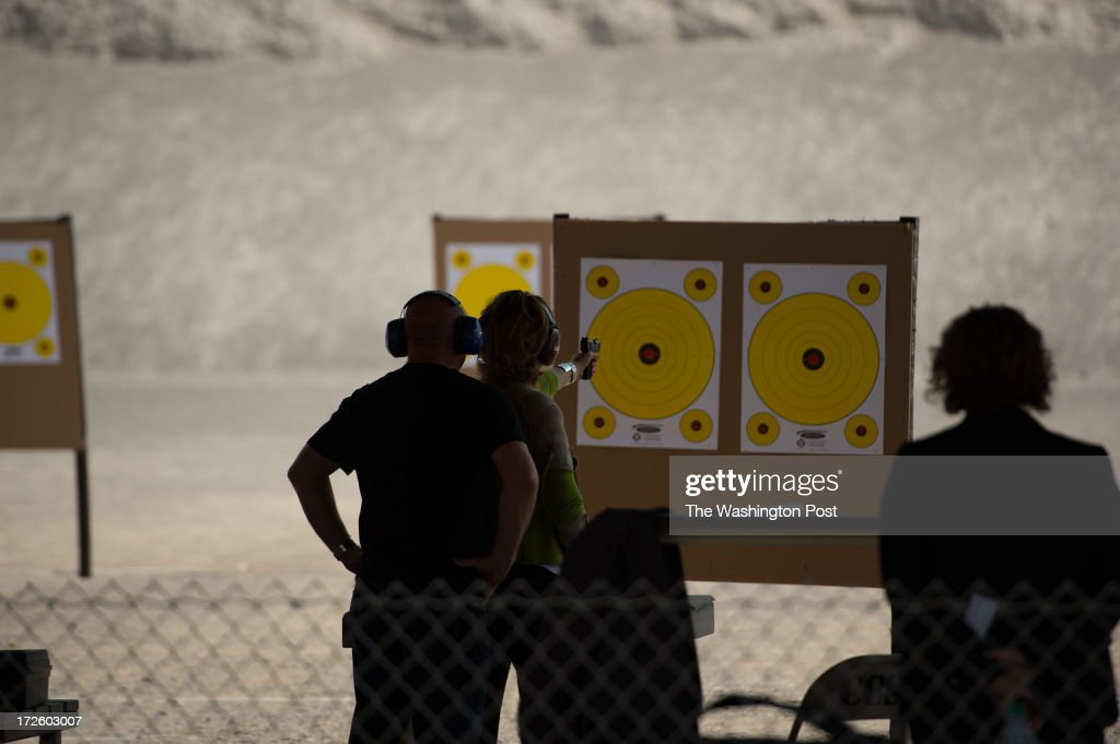 Former U.S. Representative Gabrielle Giffords fires a gun for the first time since being shot in Arizona more than 2 years ago as her husband Mark Kelly watches at Clark County Shooting Complex as they kick off their Americans for Responsible Solutions tour in Las Vegas, Nevada, on Monday, July 1, 2013. The couple are traveling to 7 states to promote safe gun legislation and chat with locals.