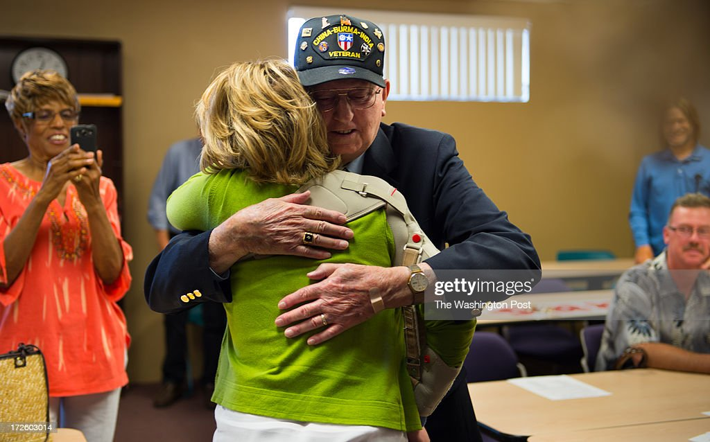 Former U.S. Representative Gabrielle Giffords is enveloped in a hug by veteran Bob Berry during the first stop on the Americans for Responsible Solutions tour in Las Vegas, Nevada, on Monday, July 1, 2013. Giffords and her husband Astronaut and Retired U.S. Navy Captain Mark Kelly are on a 7 state tour chatting with local residents about responsible gun legislation which includes background checks when buying a gun.