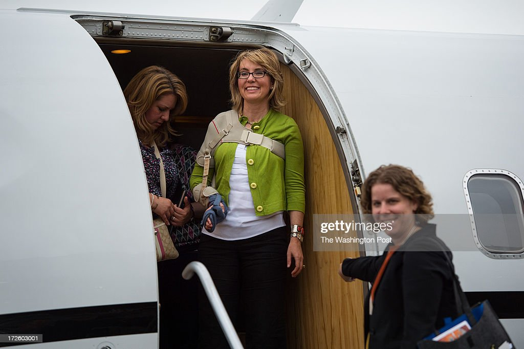 Former U.S. Representative Gabrielle Giffords looks on from the plane as her husband Mark Kelly throws the ball after their arrival at the Ted Stevens International Airport in Anchorage, Alaska, on their Americans for Responsible Solutions tour on Monday, July 1, 2013.