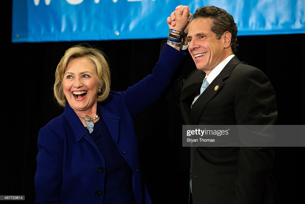 Former U.S. Secretary of State and U.S. Sen. Hillary Rodham Clinton (left to right) raises the hand of incumbent New York Governor <a gi-track='captionPersonalityLinkClicked' href=/galleries/search?phrase=Andrew+Cuomo&family=editorial&specificpeople=228332 ng-click='$event.stopPropagation()'>Andrew Cuomo</a> laugh during a 'Women for Cuomo' campaign event on October 23, 2014 at the Grand Hyatt Hotel in New York, NY. Cuomo was joined by Clinton who, citing his record on women's rights, endorsed him in the upcoming gubernatorial election on November 4, 2014. U.S. Rep. Kathy Hochul, the Democratic nominee for New York Lt. Gov., also spoke at the event.