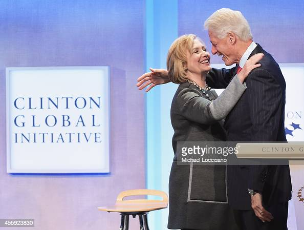 Former US Secretary of State Hillary Clinton and husband Former US President Bill Clinton embrace during the Opening Plenary Session Reimagining...
