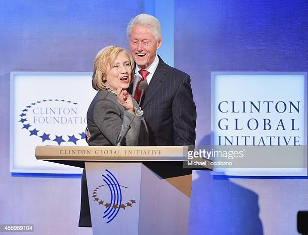 Former US Secretary of State Hillary Clinton and husband Former US President Bill Clinton address the audience during the Opening Plenary Session...
