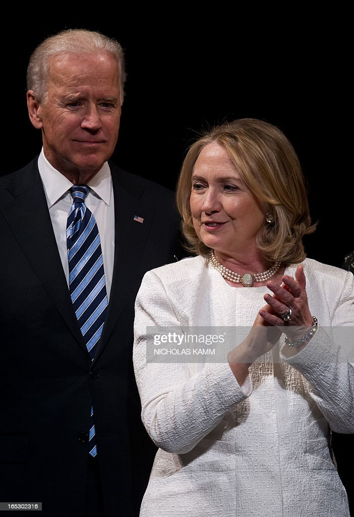 Former US Secretary of State Hillary Clinton and Vice President Joe Biden stand on stage at the end of the Vital Voices Global Awards ceremony at the Kennedy Center in Washington on April 2, 2013. The event honors 'women leaders from around the world who are the unsung heroines to strengthen democracy, increase economic opportunity, and protect human rights,' according to the group's website. AFP PHOTO/Nicholas KAMM