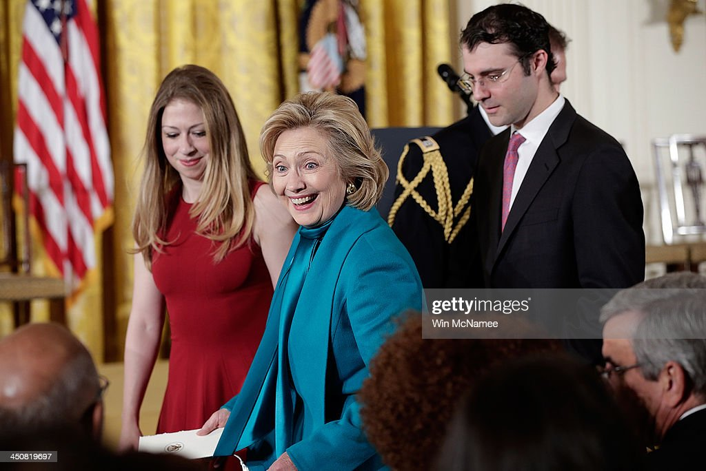 Former U.S. Secretary of State Hillary Clinton (L), her daughter Chelsea (L), and son in law Marc Mezvinsky (R) greet guests before U.S. President Barack Obama awarded former U.S. President Bill Clinton the Presidential Medal of Freedom in the East Room at the White House on November 20, 2013 in Washington, DC. The Presidential Medal of Freedom is the nation's highest civilian honor, presented to individuals who have made meritorious contributions to the security or national interests of the United States, to world peace, or to cultural or other significant public or private endeavors.