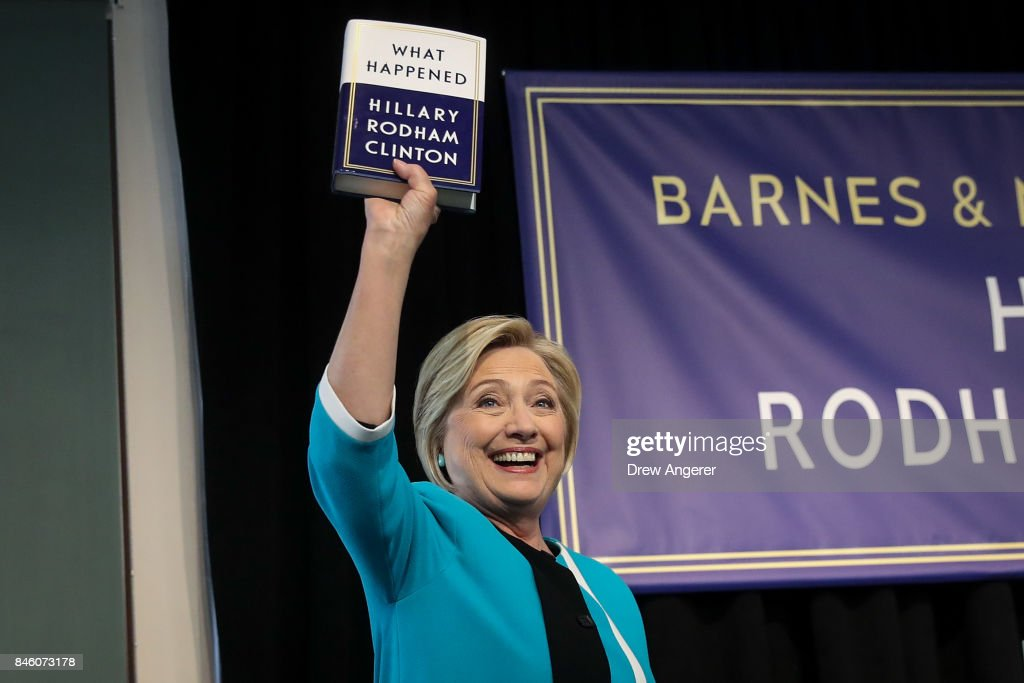 Former U.S. Secretary of State Hillary Clinton holds up a copy of her new book 'What Happened' at a book signing event at Barnes and Noble bookstore, September 12, 2017 in New York City. Clinton's book, which focuses on her 2016 election loss to President Donald Trump, goes on sale today.