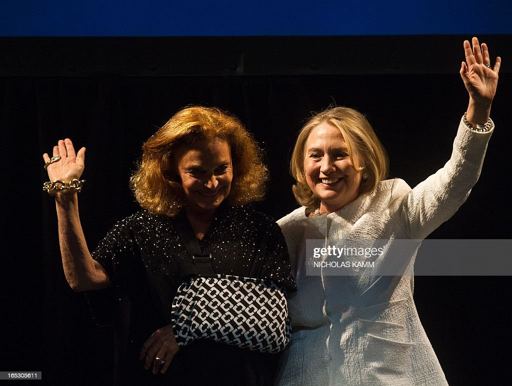 Former US Secretary of State Hillary Clinton (R) is greeted on stage by fashion designer Diane von Furstenberg before addressing the Vital Voices Global Awards ceremony at the Kennedy Center in Washington on April 2, 2013. The event honors 'women leaders from around the world who are the unsung heroines to strengthen democracy, increase economic opportunity, and protect human rights,' according to the group's website. AFP PHOTO/Nicholas KAMM