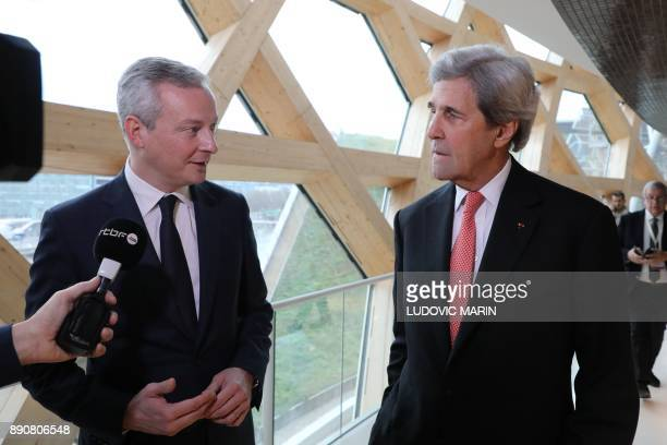 Former US secretary of state John Kerry speaks with French Minister of Economy and Finance Bruno Le Maire next to journalists during the One Planet...