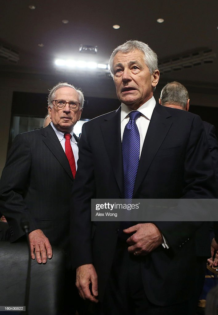 Former U.S. Sen. Chuck Hagel (R-NE) (R) arrives at his confirmation hearing to become the next secretary of defense before the Senate Armed Services Committee as former Sen. Sam Nunn (D-GA) (L) looks on January 31, 2013 on Capitol Hill in Washington, DC. President Barack Obama nominated Hagel, a controversial choice as Hagel opposed former President George W. Bush and his own party on the Iraq War and upset liberals with his criticism of a gay ambassador, for which he later apologized.