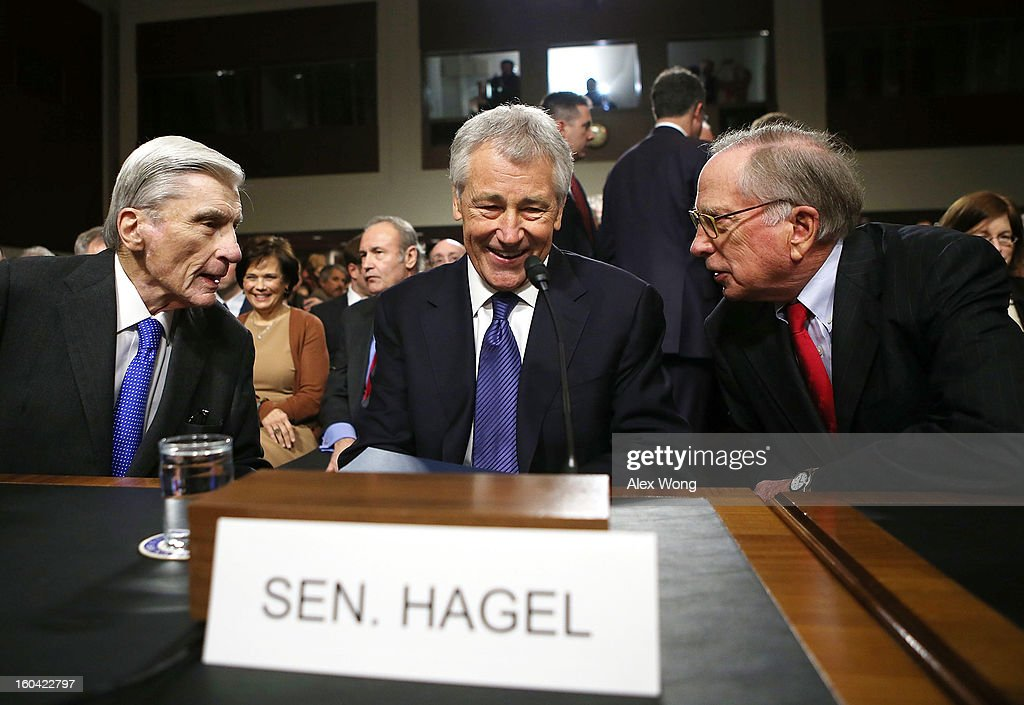 Former U.S. Sen. Chuck Hagel (R-NE) (C) share a moment with former U.S. Sen. John Warner (R-VA) (L) and former U.S. Sen. Sam Nunn (D-GA) (R) as they take their seats at Hagel's confirmation hearing to become the next secretary of defense before the Senate Armed Services Committee January 31, 2013 on Capitol Hill in Washington, DC. President Barack Obama nominated Hagel, a controversial choice as Hagel opposed former President George W. Bush and his own party on the Iraq War and upset liberals with his criticism of a gay ambassador, for which he later apologized.