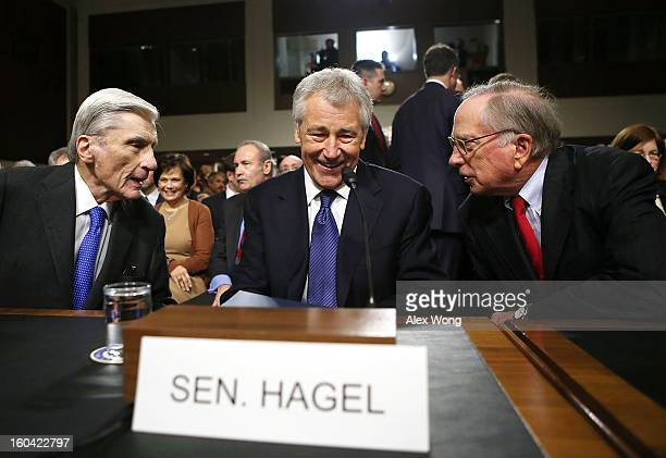 Former US Sen Chuck Hagel share a moment with former US Sen John Warner and former US Sen Sam Nunn as they take their seats at Hagel's confirmation...